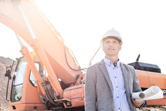 Thoughtful engineer looking away while holding blueprints by bulldozer at construction site Royalty Free Stock Image