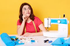 Thoughtful European young lady looks aside with interest, creating new ideas, having inspiration time, pause to sew. Modern sewing royalty free stock image