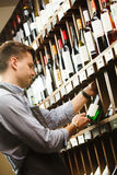 Thoughtful expert in winemaking on background of shelves with wine. Royalty Free Stock Photography