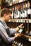 Thoughtful expert in winemaking on background of shelves with wine. Stock Images