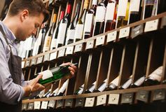 Thoughtful expert in winemaking on background of shelves with wine. Stock Photography