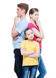Thoughtful family with daughter standing back to back at studio Royalty Free Stock Photography