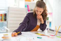 Thoughtful fashion designer working in office Stock Photography