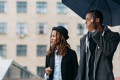 Thoughtful fashion pedestrians. Rainy mood. Young black couple with umbrella , happy African American, perspective concept royalty free stock image