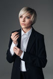 Thoughtful fashion woman buttoning her shirt Royalty Free Stock Images