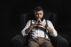 Thoughtful fashionable businessman sitting in armchair and looking at camera Royalty Free Stock Photo