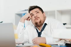 thoughtful fat businessman with laptop at workplace stock images