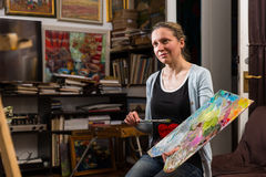 Thoughtful female artist  dreaming in her studio Stock Photography