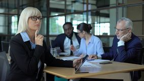 Thoughtful female boss making decision analyzing tablet report business strategy