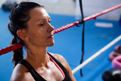 Thoughtful female boxer leaning on rope. Thoughtful female boxer leaning on boxing ring rope Royalty Free Stock Photography
