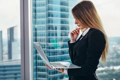 Thoughtful female CEO standing against window in her private office in modern business center holding a laptop reading stock image