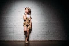 Thoughtful female child in safari costume standing. At white wall royalty free stock photography