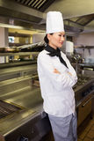 Thoughtful female cook standing in kitchen Royalty Free Stock Image