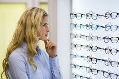 Thoughtful female customer selecting spectacles Royalty Free Stock Images