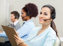 Thoughtful Female Customer Service Representative. Holding clipboard with colleagues in background at office royalty free stock image