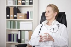 Thoughtful Female Doctor on a Chair Holding a Cup Royalty Free Stock Image