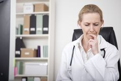 Thoughtful Female Doctor Putting Finger on Lips Stock Photos