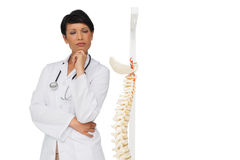 Thoughtful female doctor with skeleton model Stock Photo