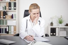 Thoughtful Female Doctor Studying Medical Findings Stock Image