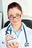 Thoughtful female doctor taking notes Royalty Free Stock Image