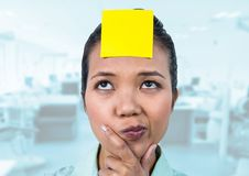 Thoughtful female executive with sticky note on head in office Stock Image