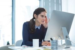 Thoughtful female executive working on computer Stock Images