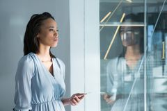 Female executives standing with mobile phone near window. Thoughtful female executives standing with mobile phone near window royalty free stock images