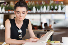 Thoughtful female freelancer studying in a caff. Young businesswoman reading her notebook in a cafe Royalty Free Stock Photos