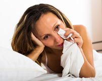 Thoughtful female lies in bed Royalty Free Stock Photography