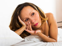 Thoughtful female lies in bedroom Royalty Free Stock Image