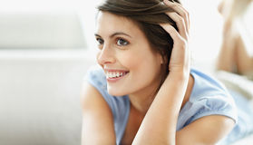 Thoughtful female lying relaxed at home Royalty Free Stock Image