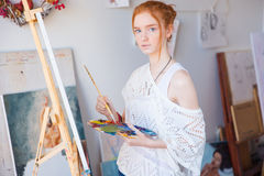 Thoughtful female painter using oil paints for painting on canvas. Thoughtful attractive young female painter using oil paints for painting on canvas in art royalty free stock image