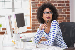 Thoughtful female photo editor in office Stock Photo