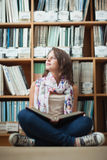 Thoughtful female student against bookshelf with a book on the library floor Stock Photo