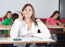 Thoughtful Female Student Looking Up At Desk. With classmates in classroom Royalty Free Stock Image