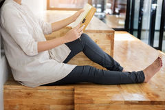 Thoughtful female student sitting Serious reading a book in a li. Brary floor, Education concept Royalty Free Stock Image
