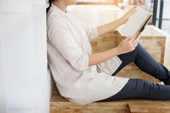 Thoughtful female student sitting Serious reading a book in a li. Brary floor, Education concept Stock Images