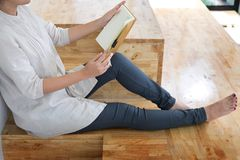 Thoughtful female student sitting Serious reading a book in a li. Brary floor, Education concept Stock Photo