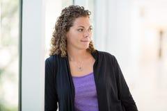 Thoughtful Female Student At University Corridor Stock Photography