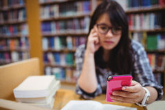 Thoughtful female student using a mobile phone Royalty Free Stock Image
