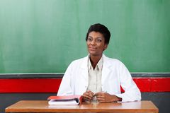 Thoughtful Female Teacher Sitting At Desk In Stock Image