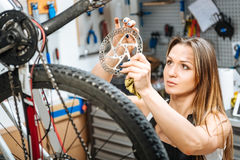Thoughtful female technician holding the cogwheel in the garage Stock Images