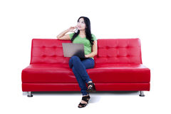 Thoughtful female using laptop on red sofa - isolated Royalty Free Stock Photo