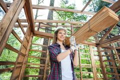 Thoughtful Female Worker Carrying Wooden Planks Stock Photos