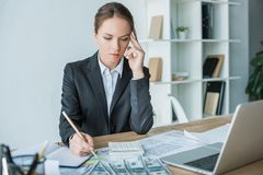 Thoughtful financier looking at calculator. In office stock photos