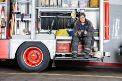 Thoughtful Firewoman Sitting In Truck Royalty Free Stock Photo