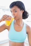 Thoughtful fit woman drinking a glass of orange juice Royalty Free Stock Photography