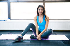 Thoughtful fit woman sitting on yoga mat Stock Images