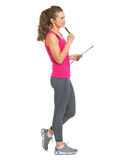 Thoughtful fitness trainer with clipboard looking on copy space Royalty Free Stock Photos
