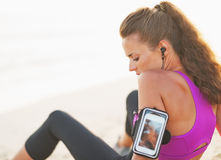 Thoughtful fitness young woman in headphones sitting on beach Stock Images